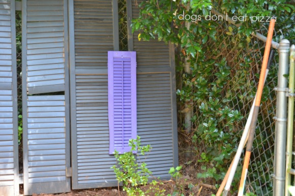 Use painted smaller shutters to cover any holes in shutters turned into a privacy screen - thediybungalow.com