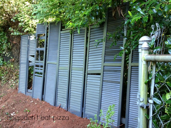Leaned the shutters up against the fence to turn shutters into a privacy screen - thediybungalow.com