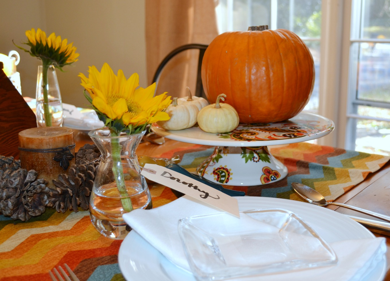 Arranging pumpkins on a colorful cake plate is an easy way to bring natural elements to your Thanksgiving table - thediybungalow.com