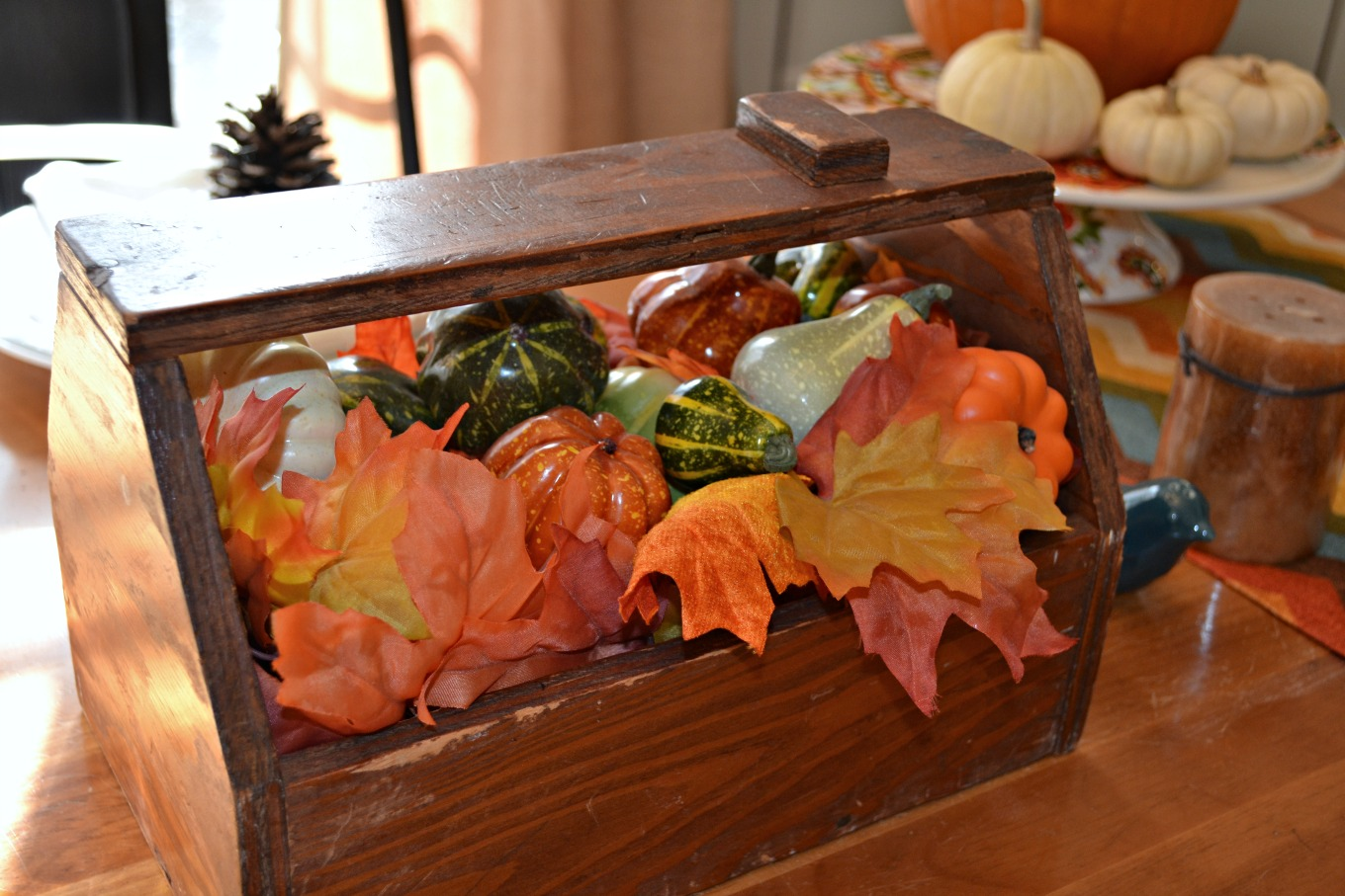 Pumpkins, gourds, and leaves in a toolbox make a centerpiece bringing natural elements to your Thanksgiving table - thediybungalow.com