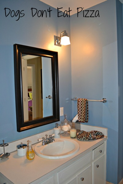 Vanity and mirror in the downstairs bathroom before - thediybungalow.com