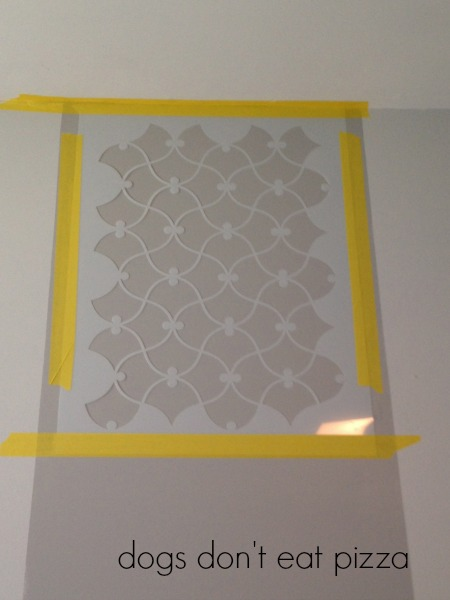 Tape the stencil to the wall with delicate-use painters tape to keep in place - thediybungalow.com