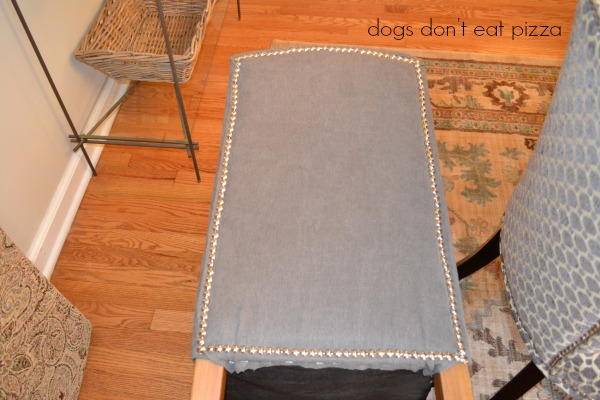 Apply the nailhead trim around the edge and over the staples - how to reupholster parsons chairs - thediybungalow.com