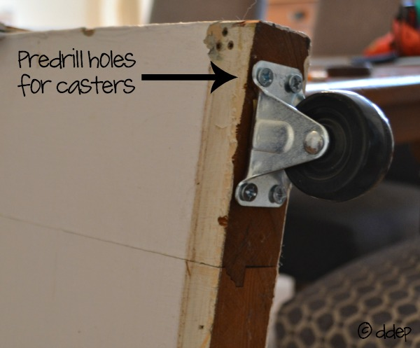Predrill holes for casters on bottom of door - How to Turn a Door into a Sliding Door - thediybungalow.com