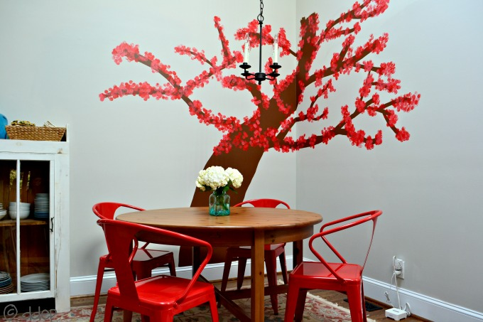 I redid my breakfast room with a bright tree and pops of red - thediybungalow.com