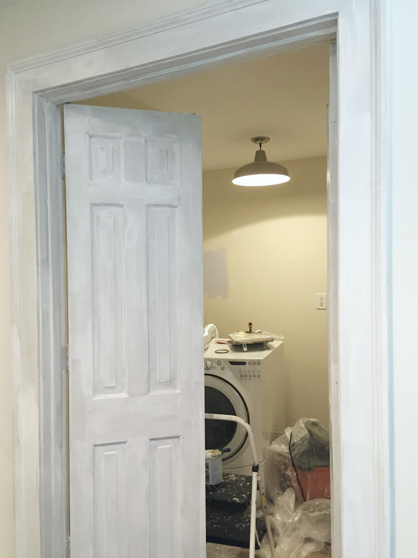 Laundry doors primed before painting white in laundry room reveal - thediybungalow.com