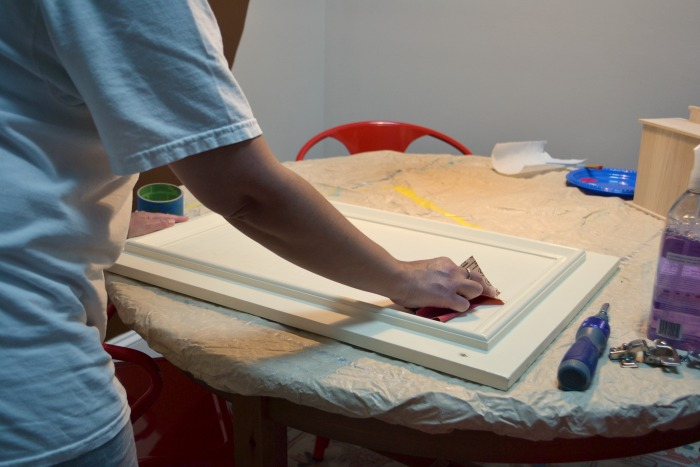 Sand the cabinet doors - How to turn a cabinet door into a memo board - thediybungalow.com