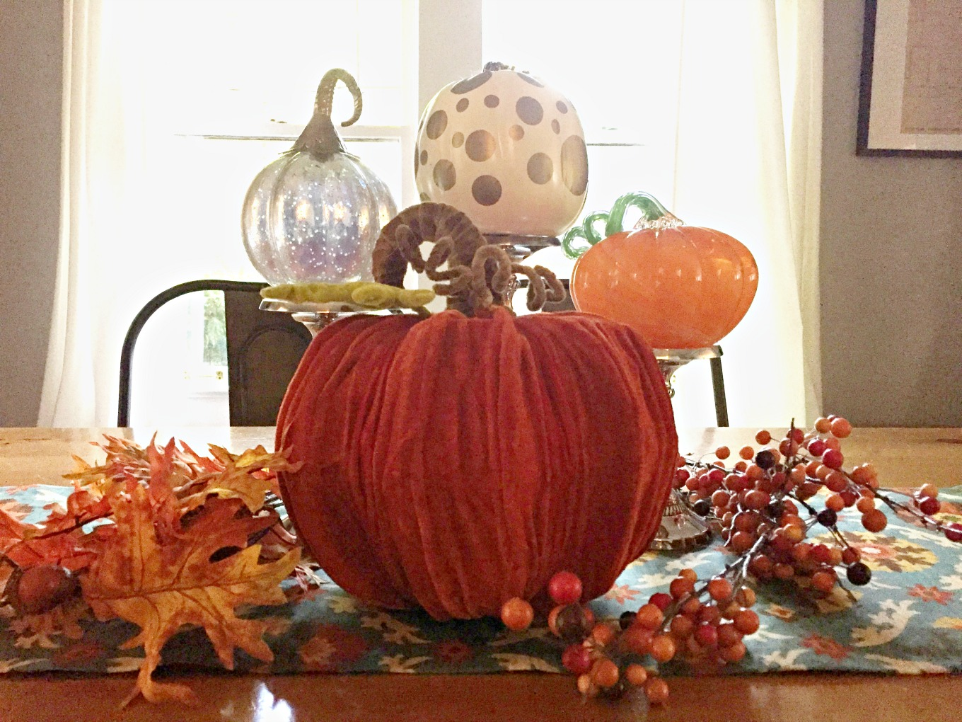 Easy fall centerpiece with pumpkins, candlesticks, and leaves - thediybungalow.com
