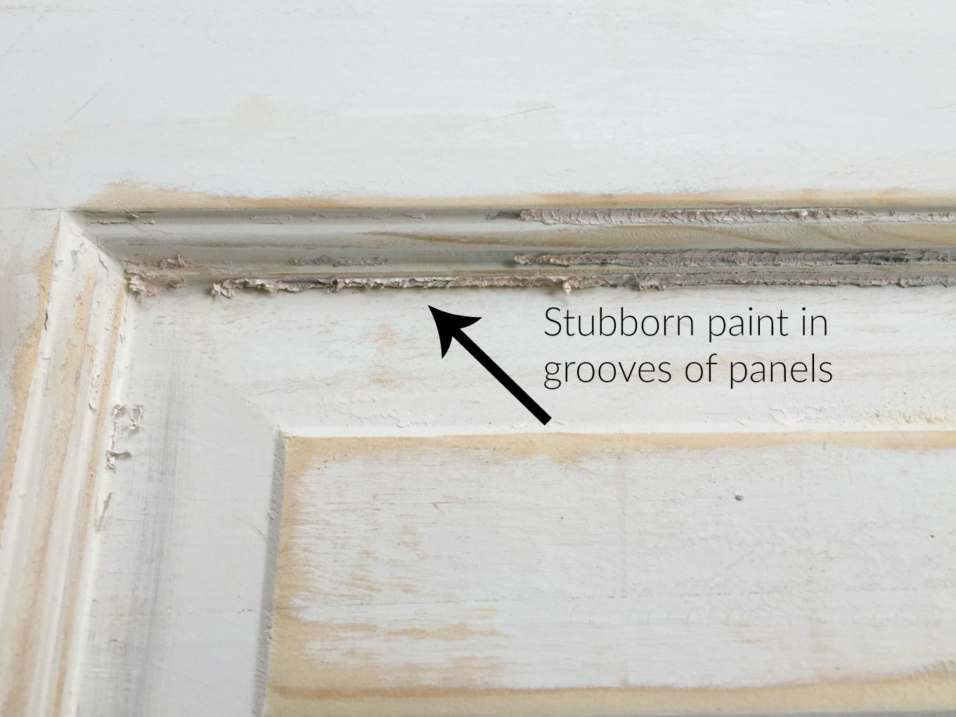 Stubborn paint in grooves of door panel after stripping - thediybungalow.com