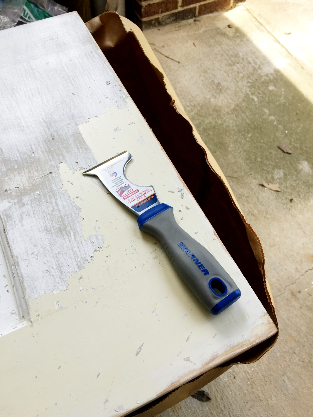 Use 5 in 1 tool to remove paint once the stripper loosens it to strip paint off wood doors - thediybungalow.com