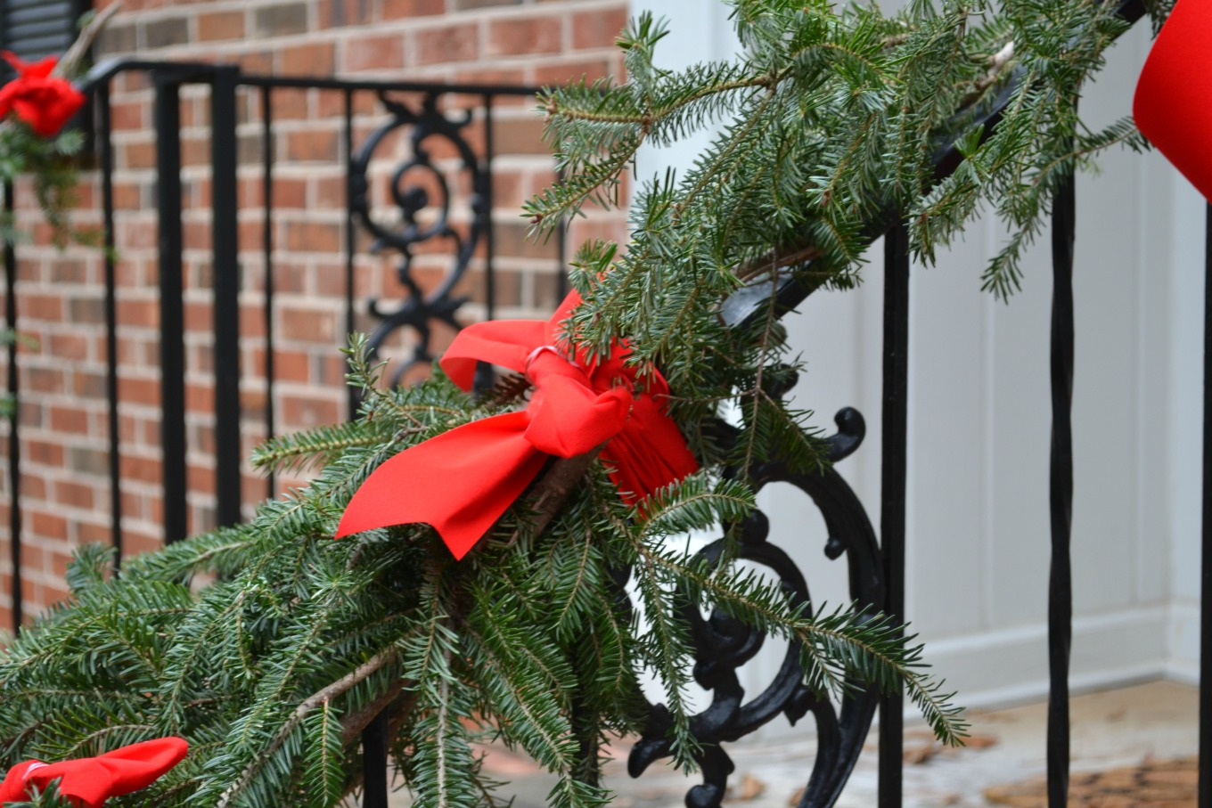 Attach pine branches to railing with ribbon to create an easy free holiday garland - thediybungalow.com